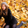 Beautiful young woman in the park autumn vibrant colors copy space — Stock Photo