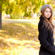 Beautiful young woman in the park autumn vibrant colors copy space — Stock Photo #21448771
