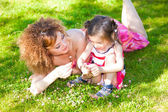 Mother and young douther picking flowers in the park on a sunny day — Stock Photo