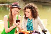 Akıllı telefonda oynamak ve sohbet river side terasında iki güzel kadın — Stok fotoğraf