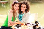 Två vackra kvinnor dricka kaffe och leende på floden sid — Stockfoto