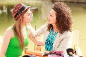 Två vackra kvinnor dricka kaffe och chattar på floden sidan terrassen — Stockfoto
