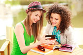 Two beautiful women playing on a smart-phone and chatting on the river side terrace — Stock Photo