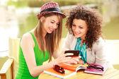 две красивые женщины, играя на смарт телефон и общаться в чате на террасе стороне реки — Стоковое фото