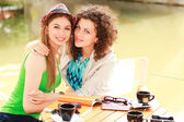 Two beautiful women drinking coffee and smiling on the river side terrace — Stock Photo