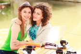 две красивые женщины пьют кофе и улыбается на террасе стороне реки — Стоковое фото