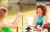 Två vackra kvinnor flickor fotografera sig med en smart-phone - levande sommar färger — Stockfoto