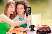 Två vackra kvinnor flickor fotografera sig med en smart- — Stockfoto