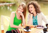 две красивые женщины, смеясь над кофе на террасе стороне реки — Стоковое фото
