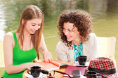 Two beautiful women chatting over a coffee at the river side terrace — Stock Photo