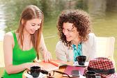 две красивые женщины, беседа за чашкой кофе на террасе стороне реки — Стоковое фото