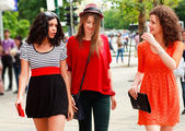 Three beautiful women walking and smiling on the street - sunny day — Stok fotoğraf
