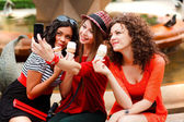 Three beautiful women photographing themselves eating icecream — Stok fotoğraf