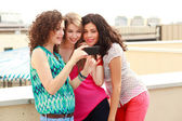 Tre vackra kvinnor som söker på en smartphone — Stockfoto