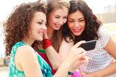 Drei schöne frauen, die auf der suche auf einem smartphone — Stockfoto
