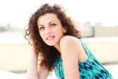 привлекательные женщины с вьющимися волосами позирует открытый в солнечный день — Стоковое фото