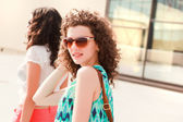 красивые женщины с вьющимися волосами позирует открытый в солнечный день — Стоковое фото