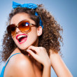 Cute pin up girl with curly hair and perfect teeth on blue background - Stok fotoğraf