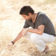 Man on dry meadow picking grass straws to start a fire, wide angle view - into the wild series — Stock Photo