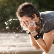 Stock Photo: Mwashes his face with water from river