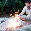 Man preparing  a fire on the beach by the river - Stock Photo