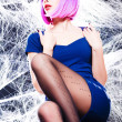 Sexy woman with purple wig and intense make-up trapped in a spider web - fashion shoot — Stock Photo