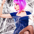 Stock Photo: Sexy model with purple wig and intense make-up trapped in spider web - fashion shoot