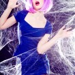 Sexy model with purple wig and intense make-up trapped in a spider web - fashion shoot - Stock Photo
