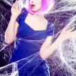 Sexy model with purple wig and intense make-up trapped in a spider web - fashion shoot — Stock Photo