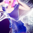 Stock Photo: Sexy woman with purple wig and intense make-up trapped in a spider web screaming- fashion shoot