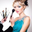 make-up artist in action on beautiful doll face - blue eyes and blond hair — Stock Photo