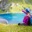 Cute girl standing on a hill pointing at a beautiful scenary — Stock Photo