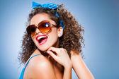 симпатичные контактный девушка с вьющимися волосами и совершенные зубы на синем фоне — Стоковое фото