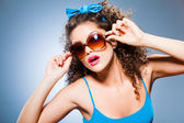 Cute pin up girl with curly hair and perfect teeth on blue background — Stock Photo