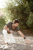 Rough man picking wood to make fire by the river - into the wild series — Stock Photo