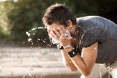 Man washes his face with water from the river — Stock Photo