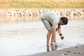 Man looking for shells by the river- into the wild series — Stock Photo