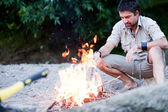 Man preparing a fire on the beach by the river — Stock Photo