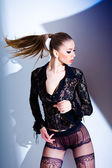 Sexy model dressed in lace blouse and elegant tights posing dynamic - fashion shoot — Stock Photo