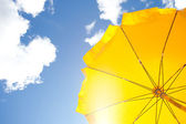 Yellow umbrella on blue sky with clouds — Stock Photo