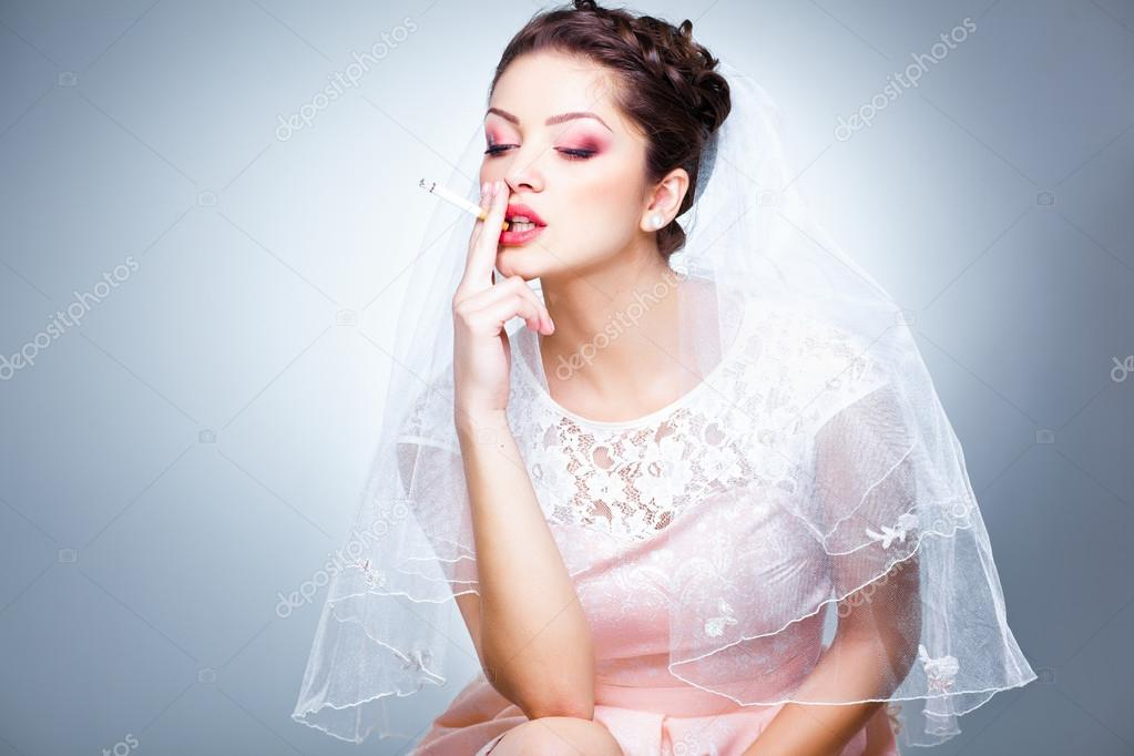 Portrait of beautiful bride smoking a cigarette funny picture