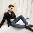 Attractive man dressed in jeans and boots in a grungy scenary — Stock Photo