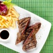 Delicious steak with french fries and souce on dish, bambus back - Stock Photo