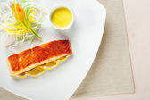Delicious fish, salad lemons and souce on dish — Stock Photo