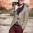 sexy fashion man model dressed elegant holding a bag posing outd — Stock Photo