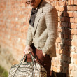 Stock Photo: Sexy fashion man model dressed elegant holding a bag posing outdoor
