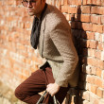 Sexy fashion man model dressed elegant holding a bag posing outdoor — Stock Photo