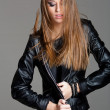 Sexy model wearing leather jacket and black skirt posing fashion in the studio - Stock Photo