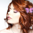Pretty woman with a butterfly in her hair - beauty shot — Stock Photo