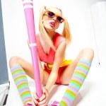 Sexy baseball girl wearing colorfull clothes posing with a baseball bat — Stock Photo